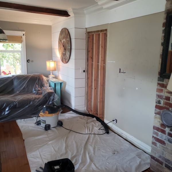 living room with doorway being boarded up