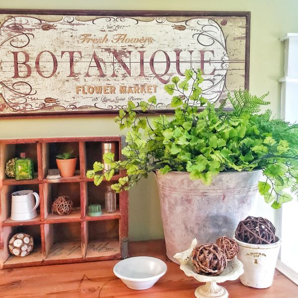 faux greenery in a metal bucket with botanique flower market sign