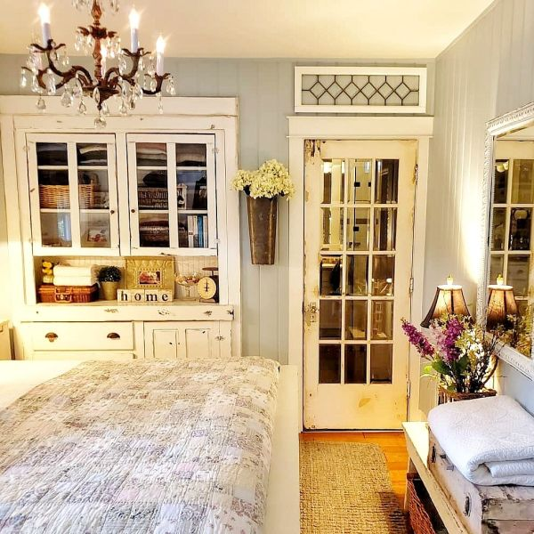 Chippy painted glass cabinet, French door, chandelier and quilt in cottage bedroom