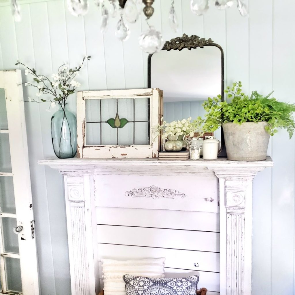 mirror, stained glass window and spring home decor on mantel