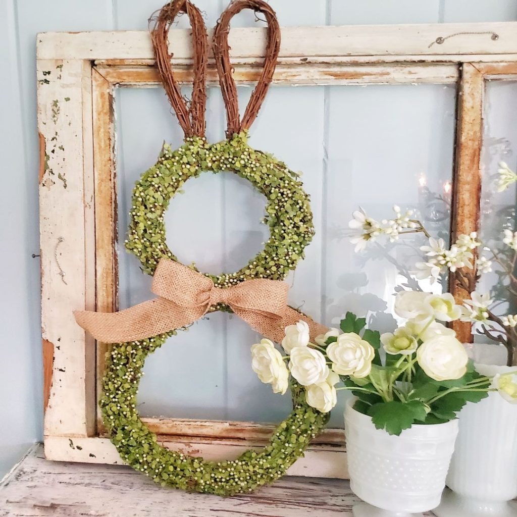 bunny wreath, spring flowers and vintage window on a bedroom mantel