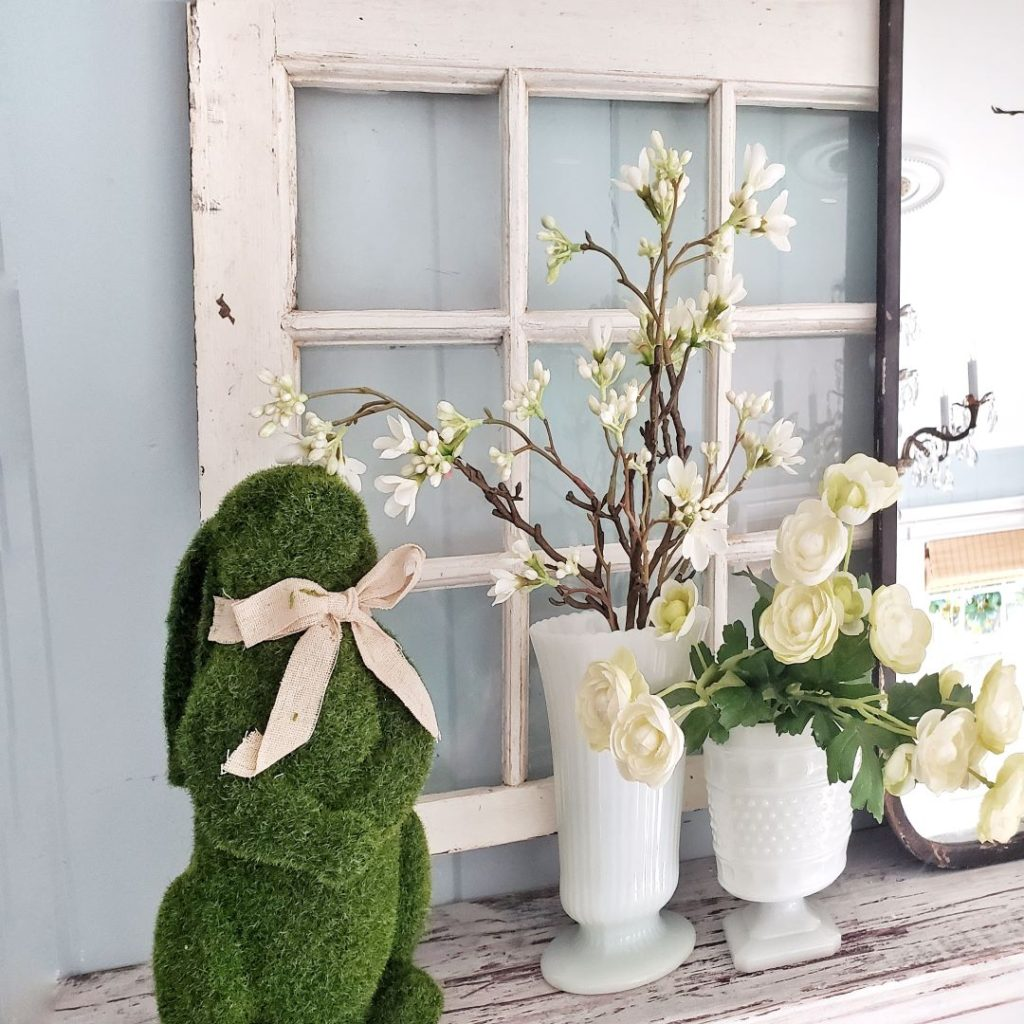 Moss bunny and spring flowers on mantel
