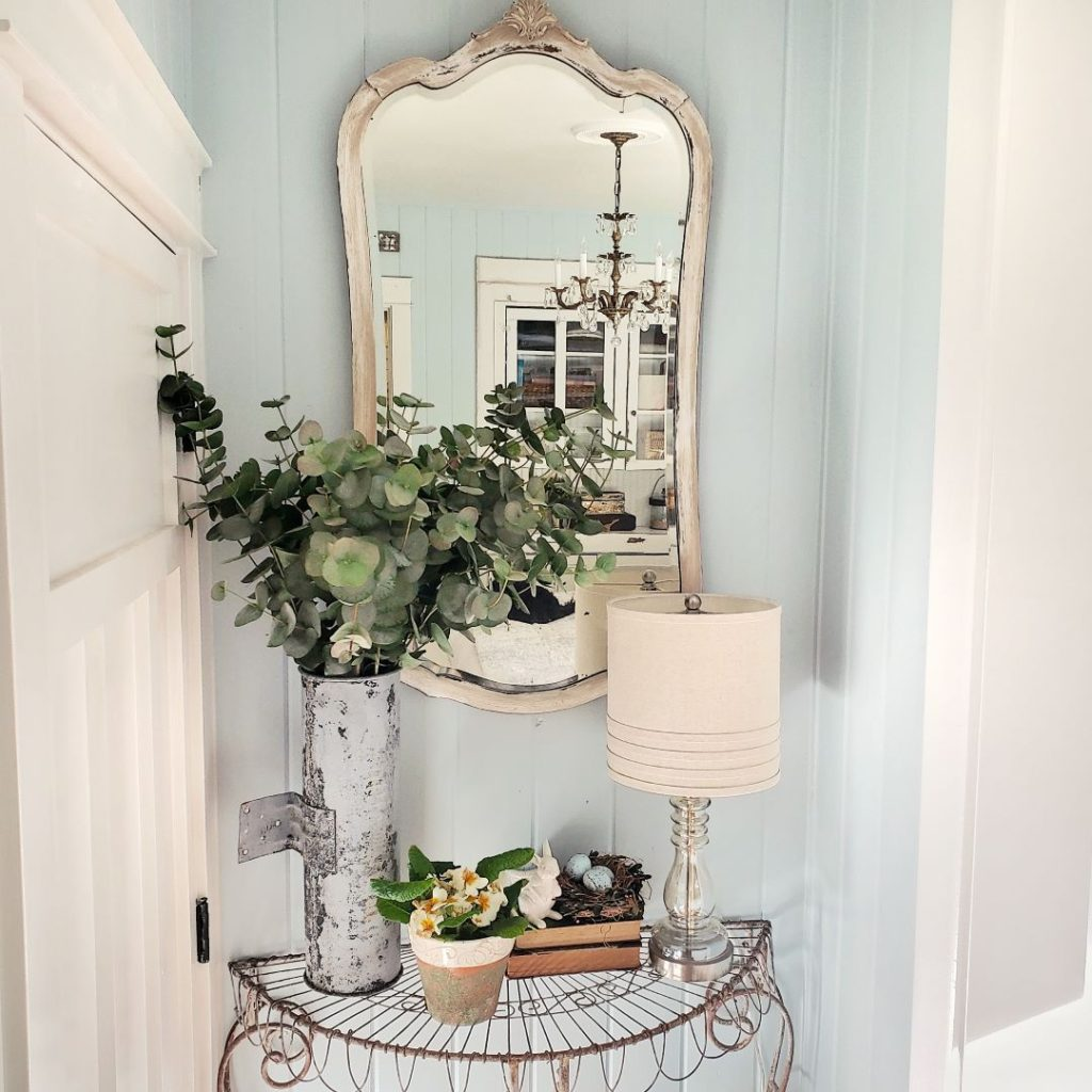 eucalyptus in a vintage container on iron table, mirror, and spring home decor
