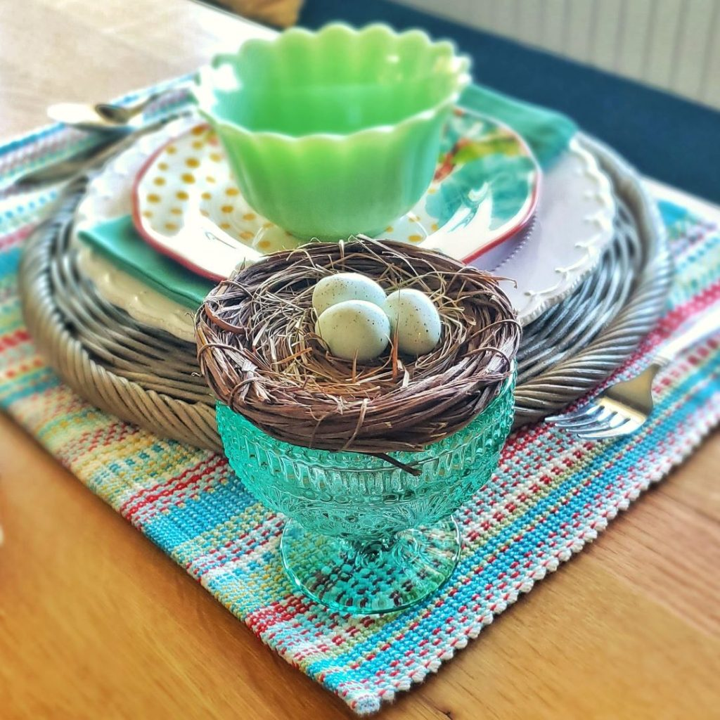 This Easter table place-setting consists of a nest full of eggs.