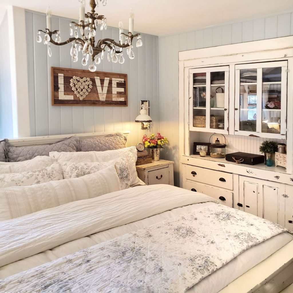 bedroom with spring bedding, built in, chandelier and love sign