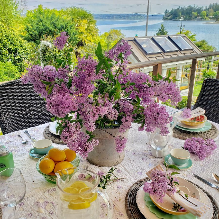 AN outdoor spring tablescape with lilacs as a centerpiece