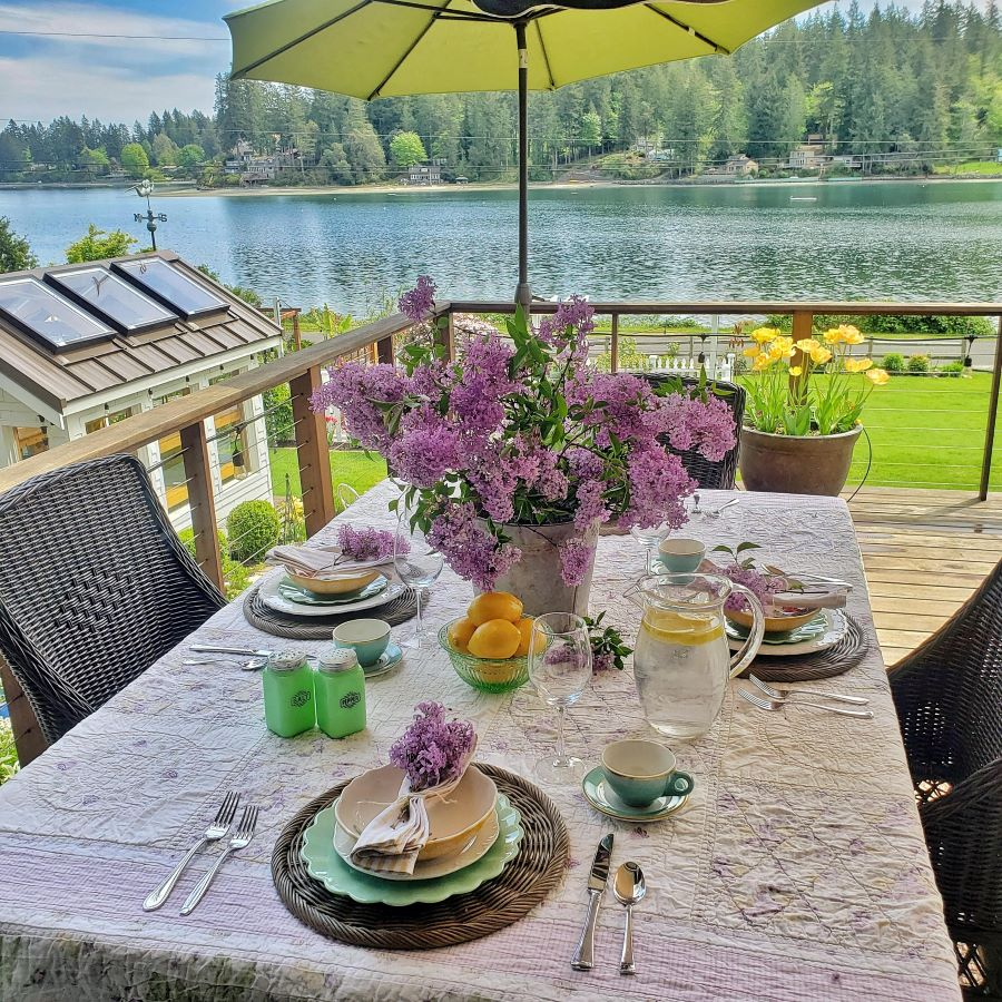 An outdoor spring tablescape out on the deck, with lilacs and over looking the bay