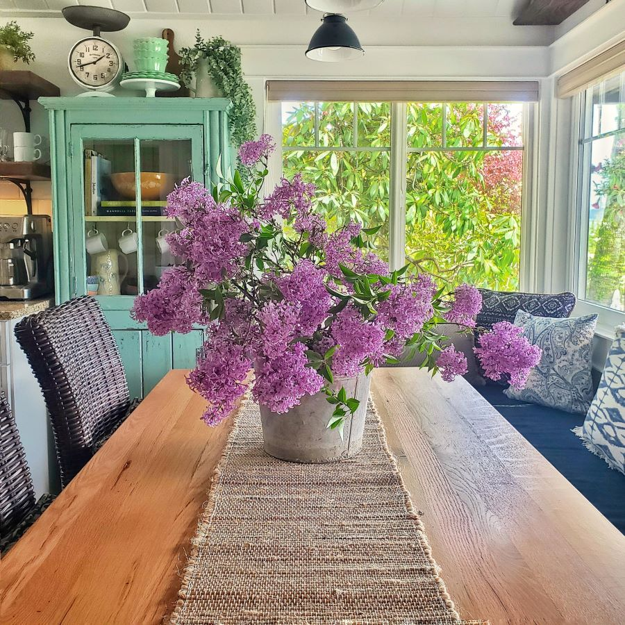 Vintage bucket of lilacs on farm table in a cottage kitchen.