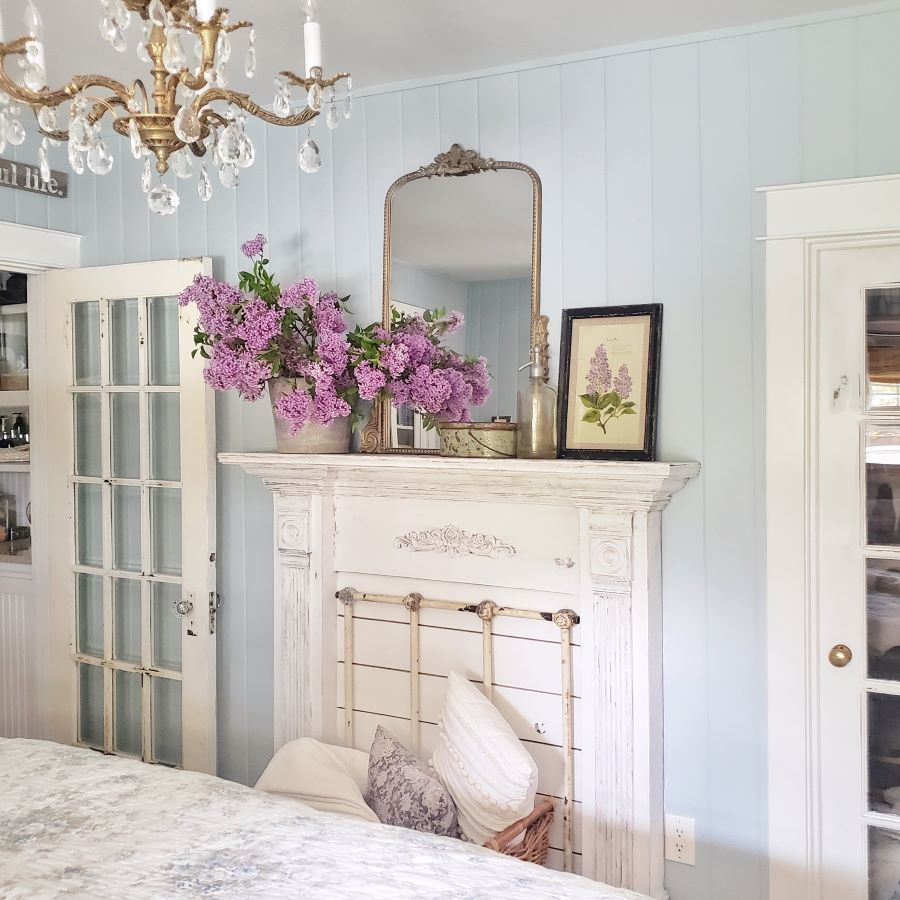 Lilacs and mirror on a fireplace mantel