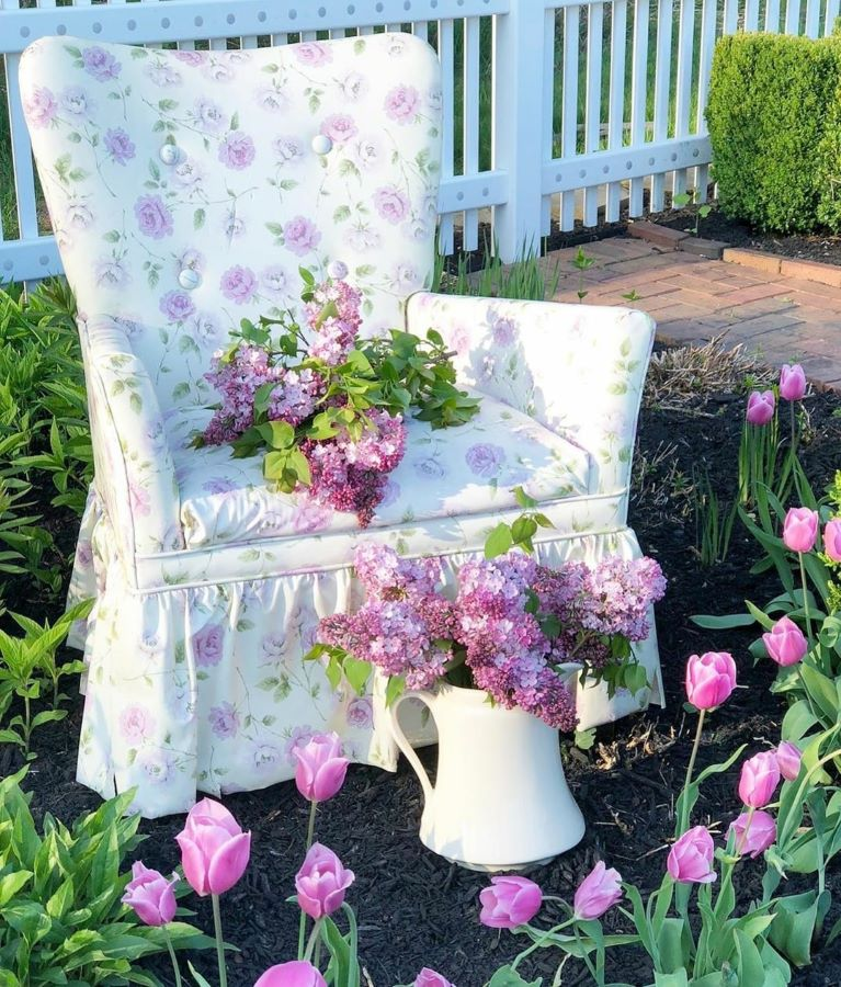 Patterned chair surrounded by lilacs.