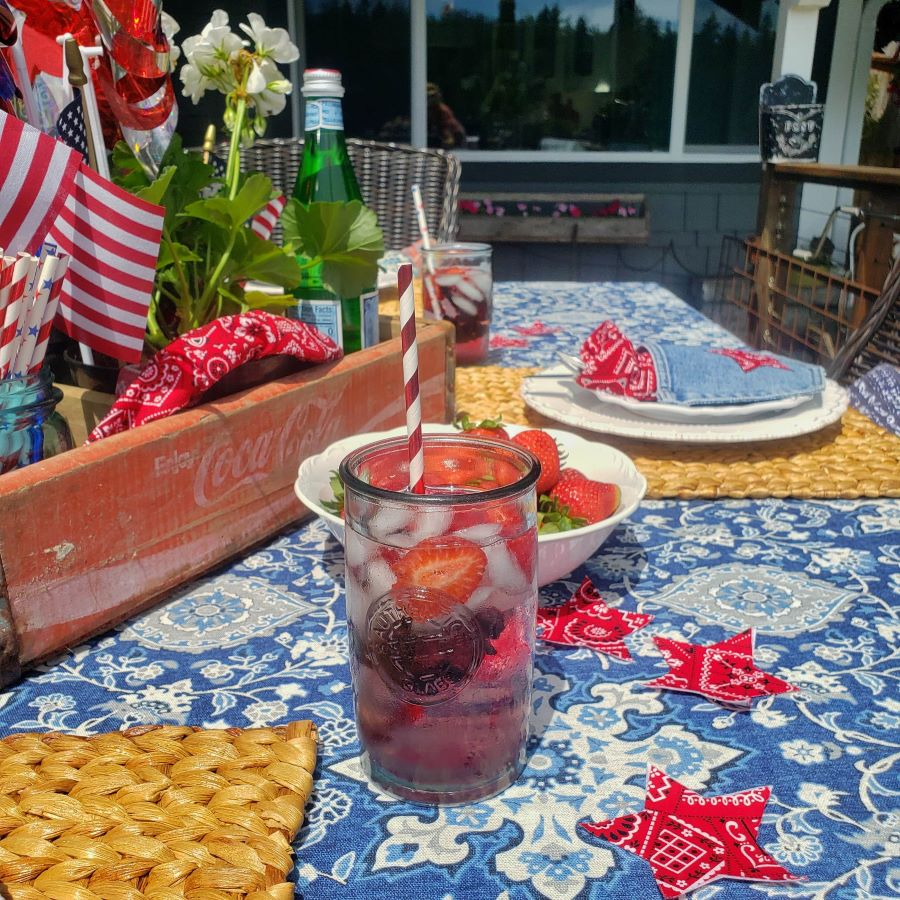 a perfectly patriotic tablescape with glass of water with berries and patriotic decor