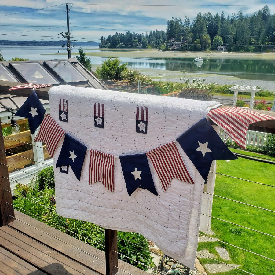 Patriotic quilt and banner hanging on deck railing