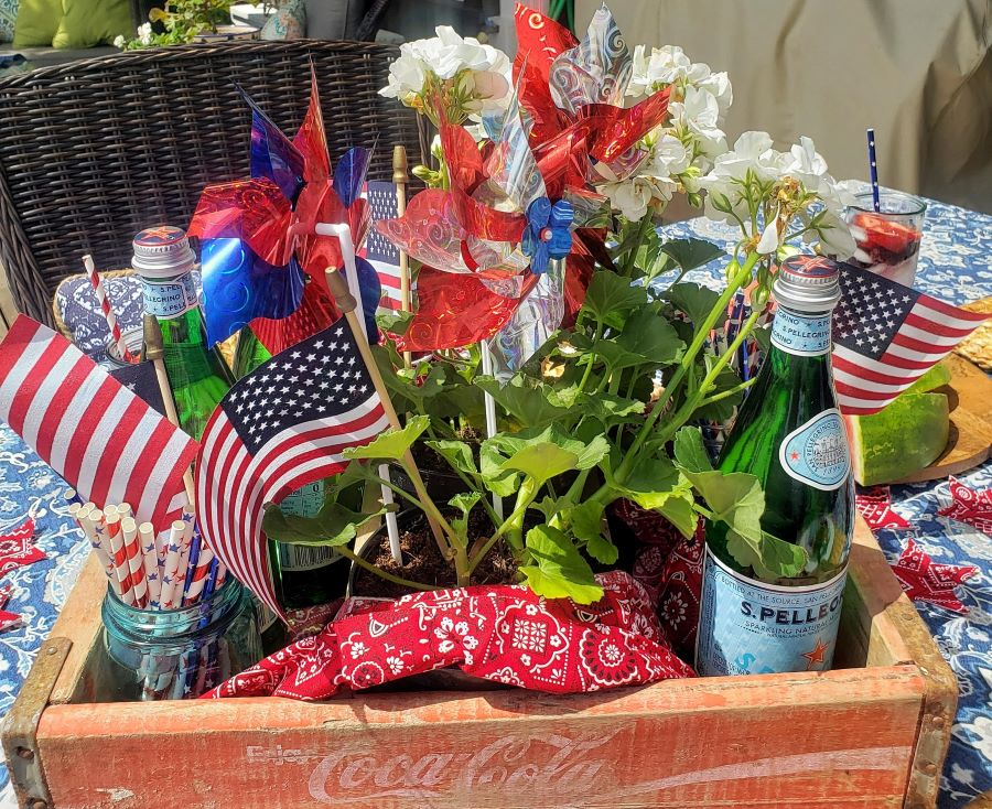 Patriotic centerpiece with red Coca Cola crate, white geraniums, American flags and pinwheels.