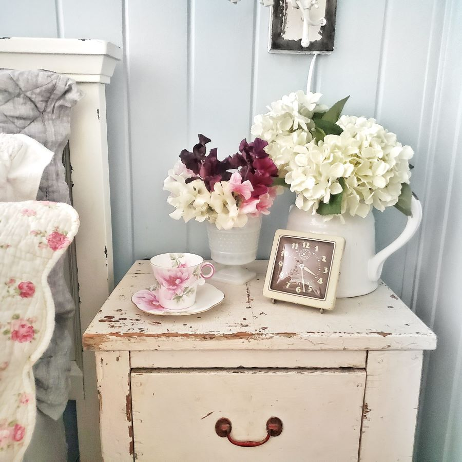 The rose traveling teacup sitting on a vintage nightstand with fresh flowers