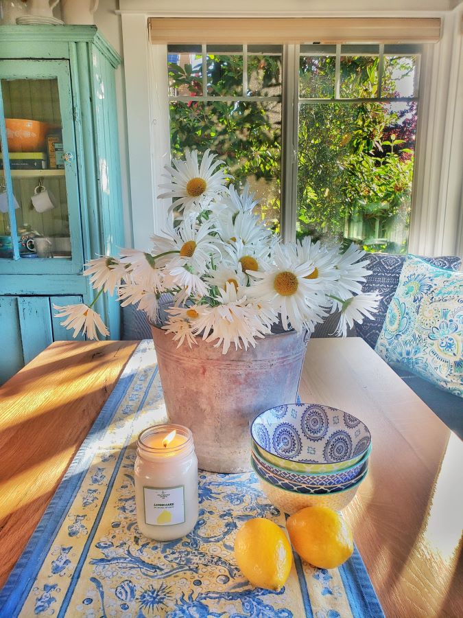 bucket full of daisies and candle on farm table