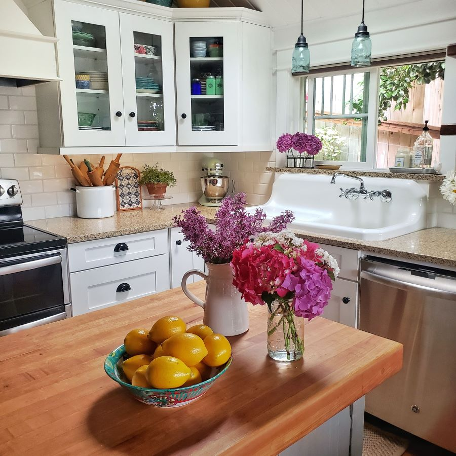 Flowers and lemons on a butcher block island, with farm sink in background