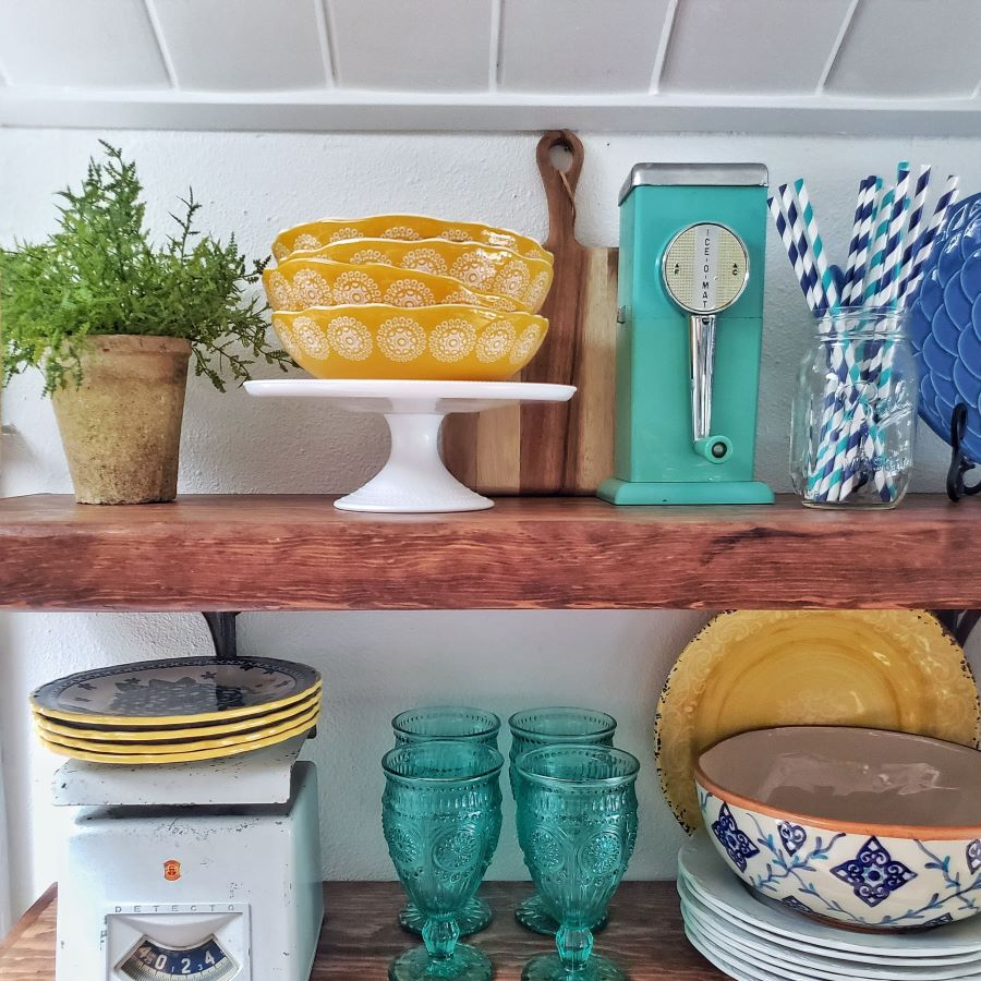 open shelving with yellow and turquoise dishes and glasses