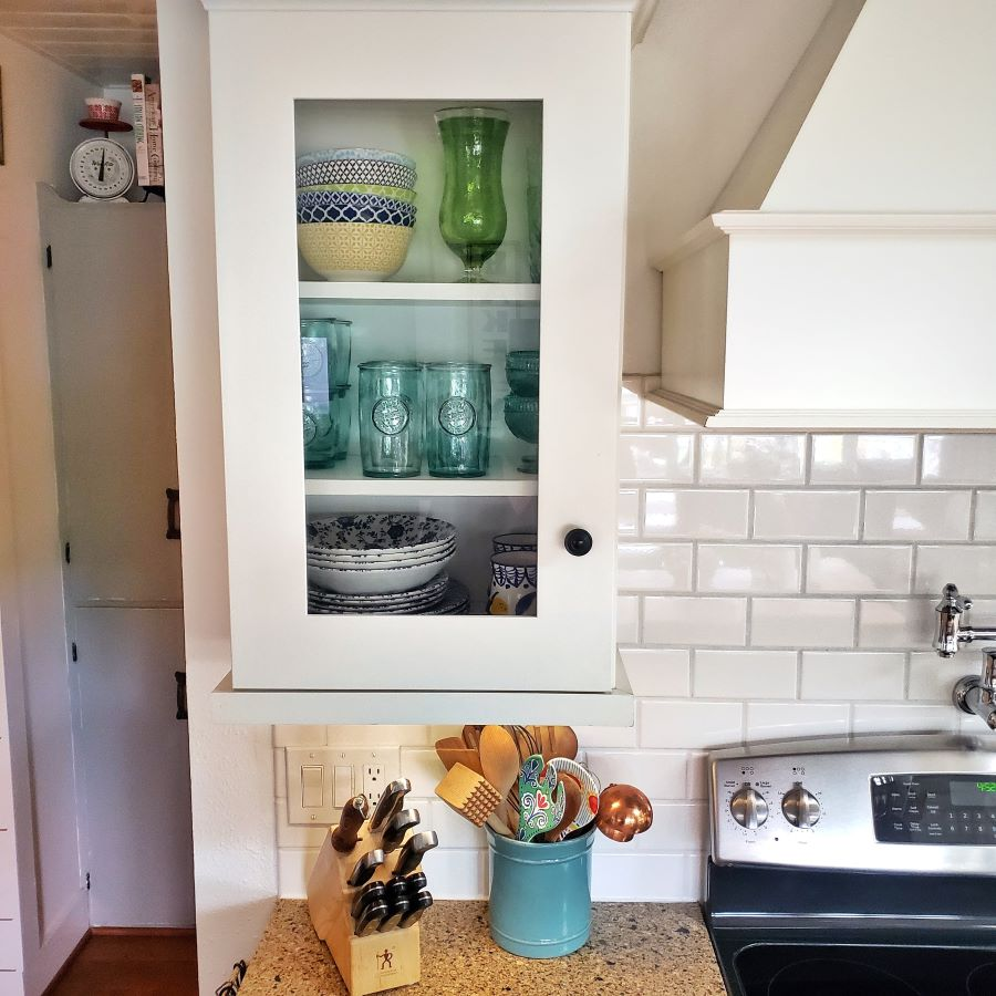 blue, green and yellow in a glass kitchen cabinet