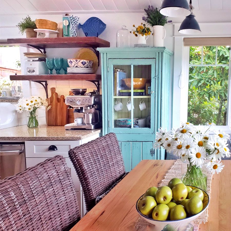 turquoise glass cabinet, open shelving and farm table with daisies