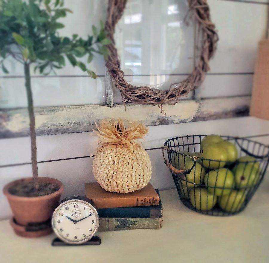 Fall vignette with pumpkin, vintage books and basket of green apples.