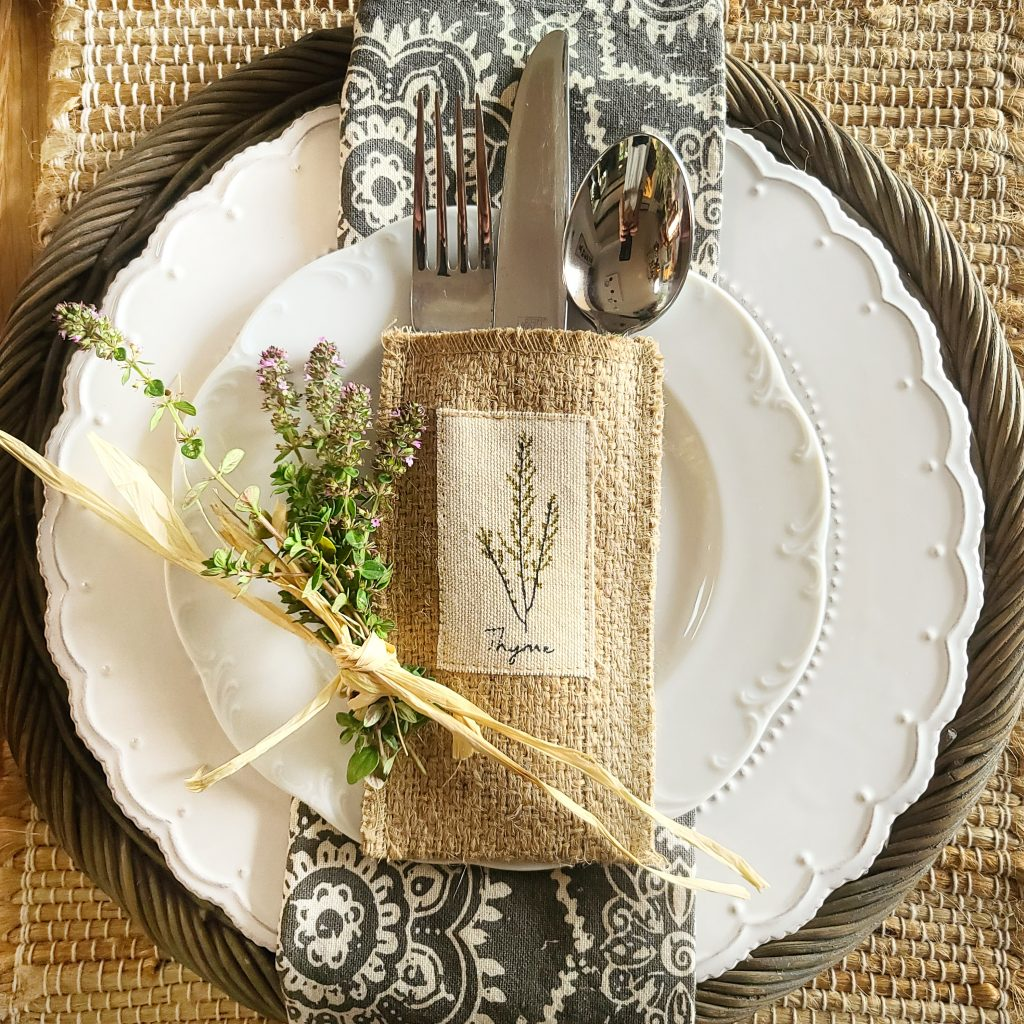 table setting with silverware pouch and herbs