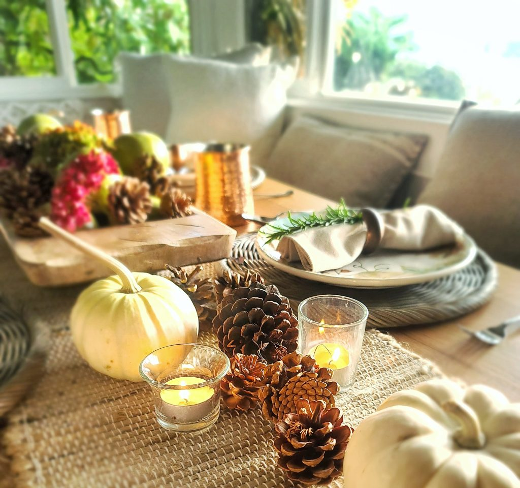Pumpkins and pinecones on table with candles