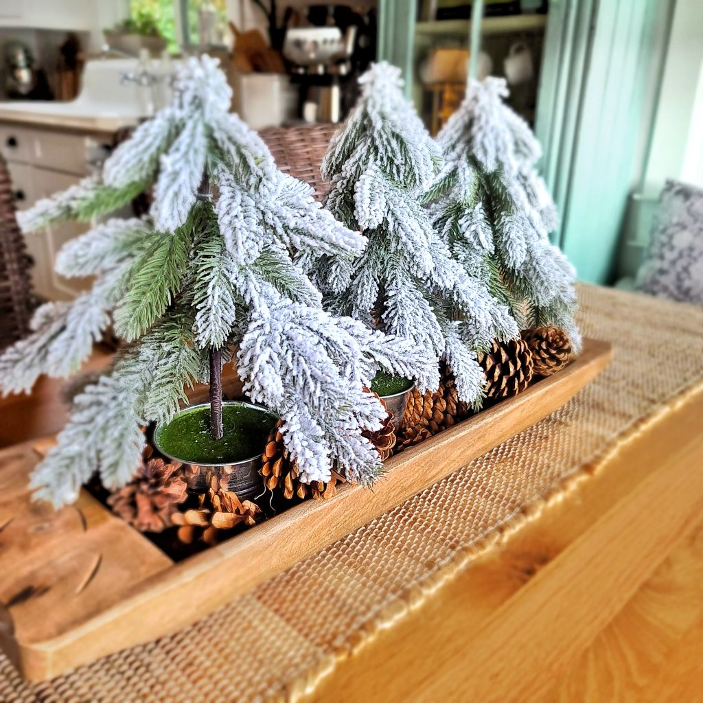 Faux artificial Christmas trees in a dough bowl