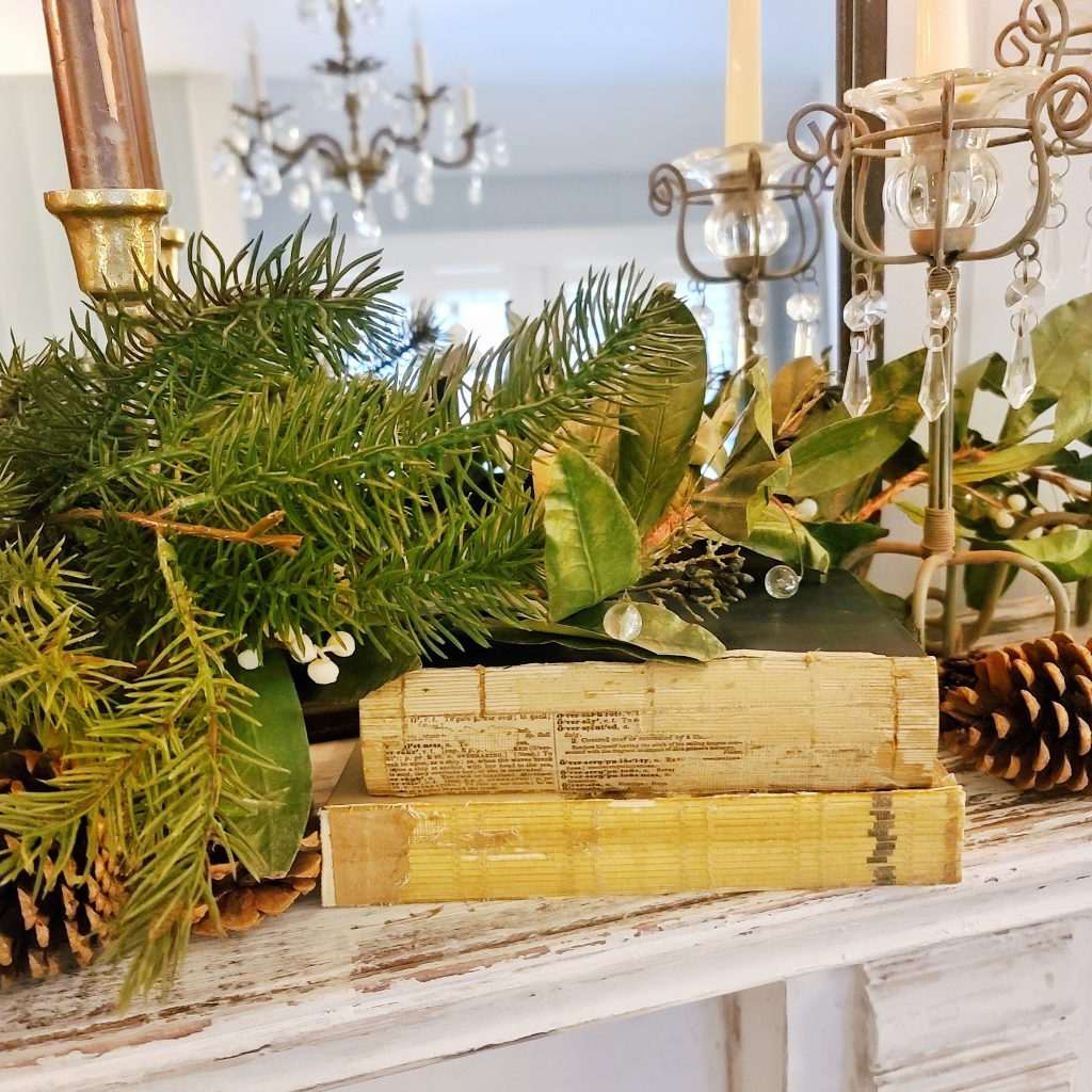 greenery, candles and pinecones on a fireplace mantel for warm and cozy winter decor